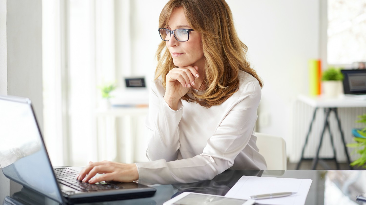 woman looking at her laptop | IRA Definition | Easy To Understand Answers To Your IRA Questions | IRA definition | traditional IRA | Featured