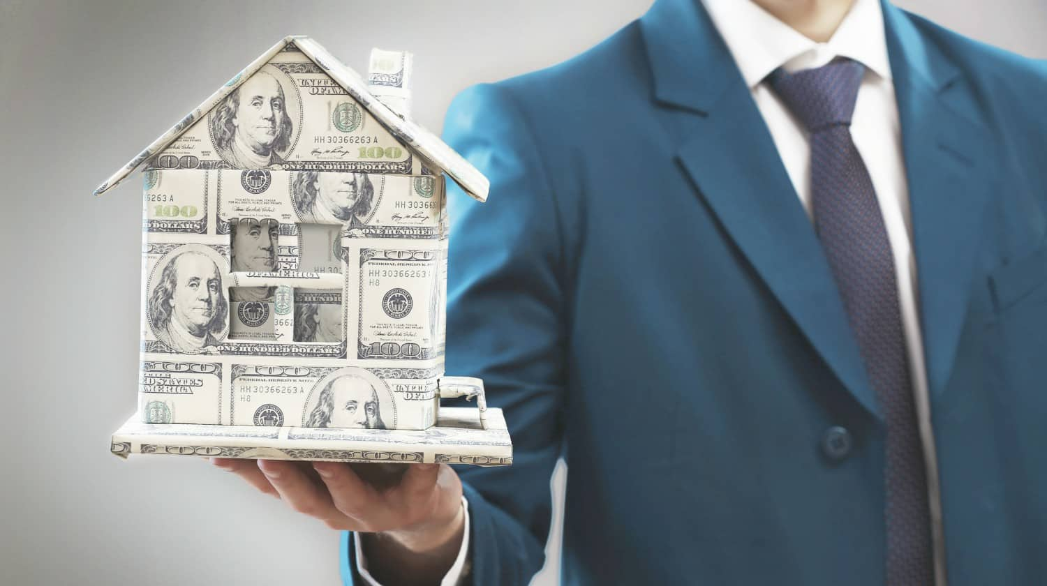 businessman holding a model house made of money   How To Start Investing In Real Estate Inside Your IRA   how to start investing in real estate   how to start investing in real estate   Featured