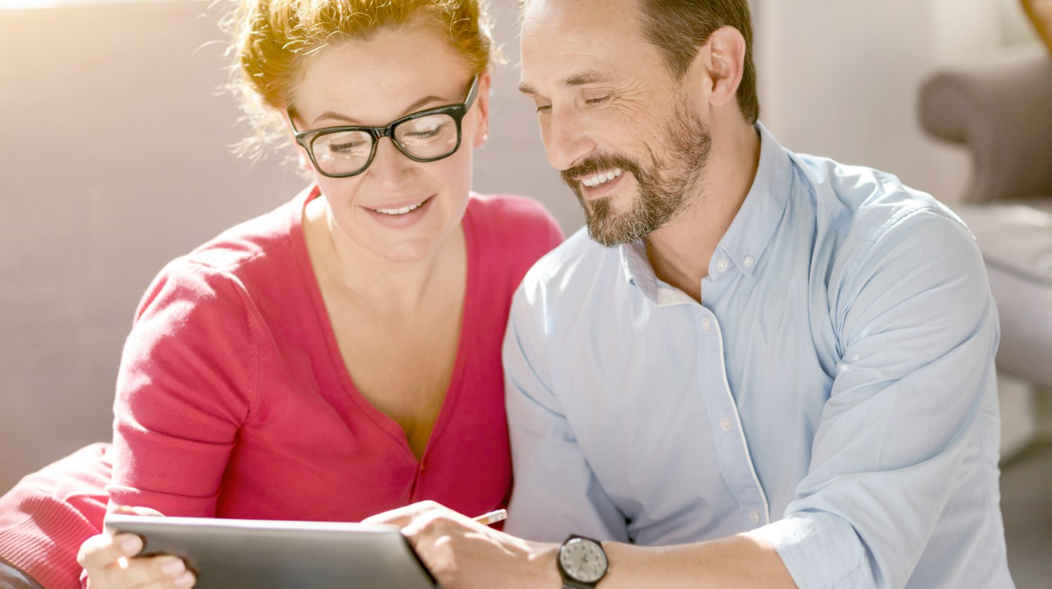 couple relaxing at home holding a tablet | What Are Traditional IRA Contribution Limits? | traditional IRA contribution limits | employer-sponsored retirement plan | Featured