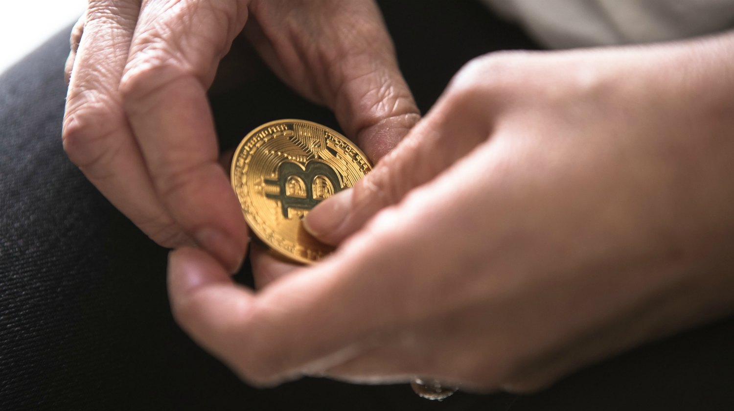 person holding round gold-colored Bitcoin | Investing in Cryptocurrency | What You Should Ask | investing in cryptocurrency | earn bitcoins | Featured