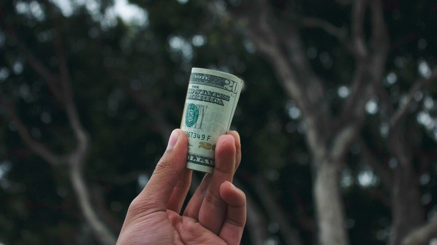 hand holding rolled up money | The Survivalist Retirement Guide: Your Foolproof Strategy Inside Your IRA | survivalist retirement guide | survival guide | Featured