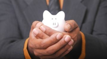 man holding piggy bank | SEP IRA Rules | Everything You Need To Know | contributions | Featured