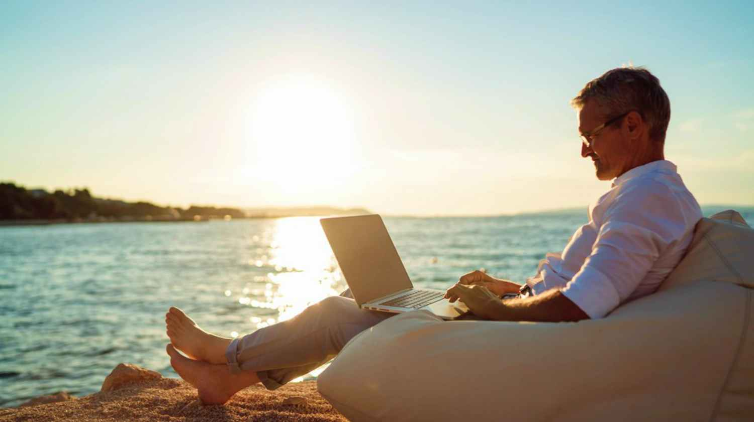 Feature | man working on laptop by the beach | How To Retire At 50 | Inside Your IRA | how much do I need to retire