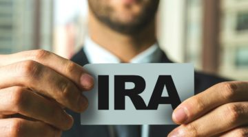 Feature | man holding ira paper | Types of IRAs | A Savings Comparison Inside Your IRA | withdraw a yearly set amount