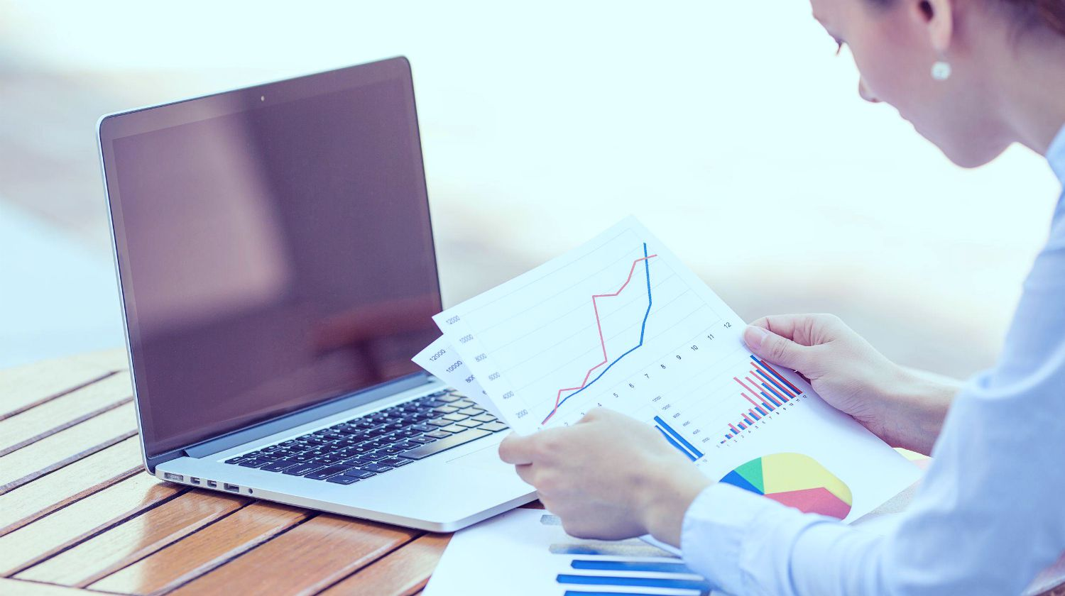 woman looking at graphs | How To Invest In Dividend Stocks Inside Your IRA | dividend | dividend stocks | Featured