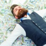 Featured | Business man lying in banknotes | How To Become A Millionaire with Roth IRA | Inside Your IRA
