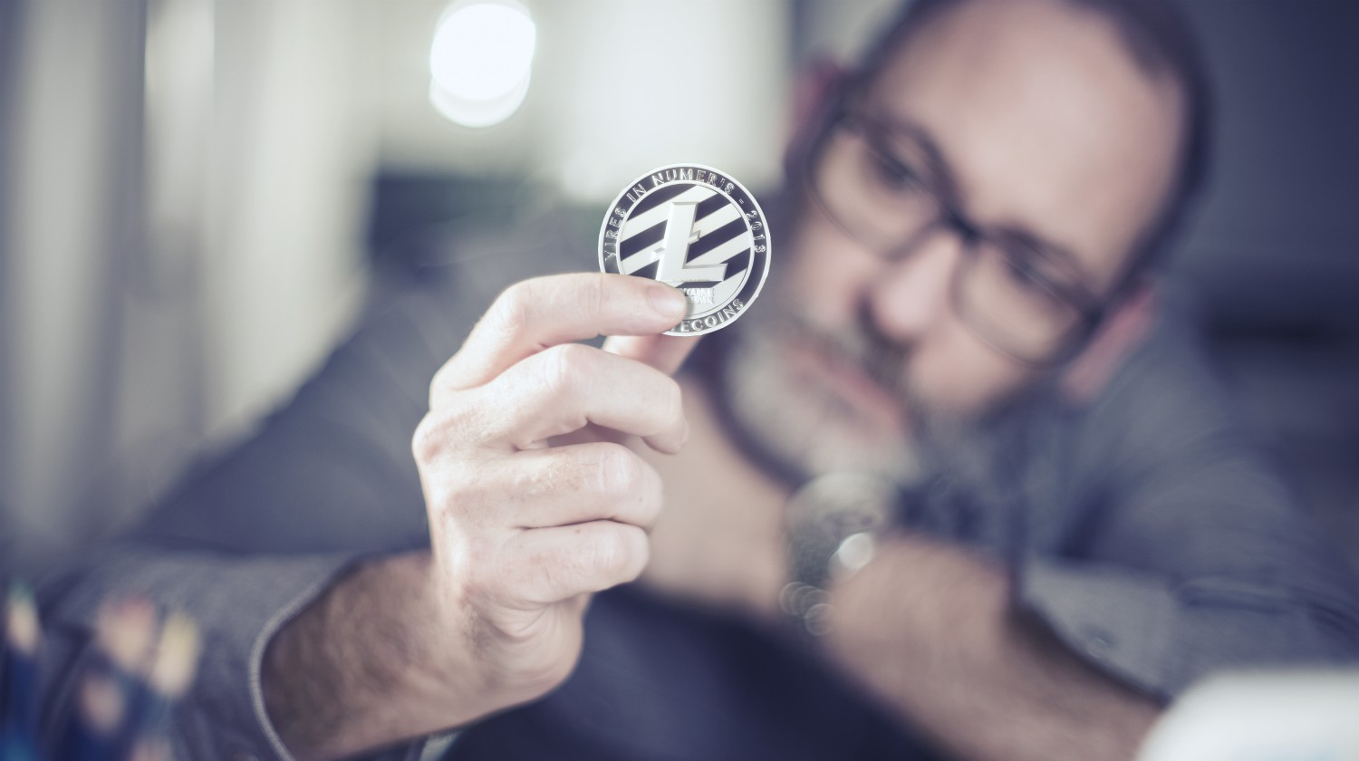 Featured | man holding litecoin | Most Promising Cryptocurrencies Other Than Bitcoin | Inside Your IRA | most promising cryptocurrencies | most promising cryptocurrency